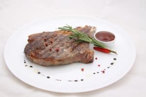 Steak resting on white plate