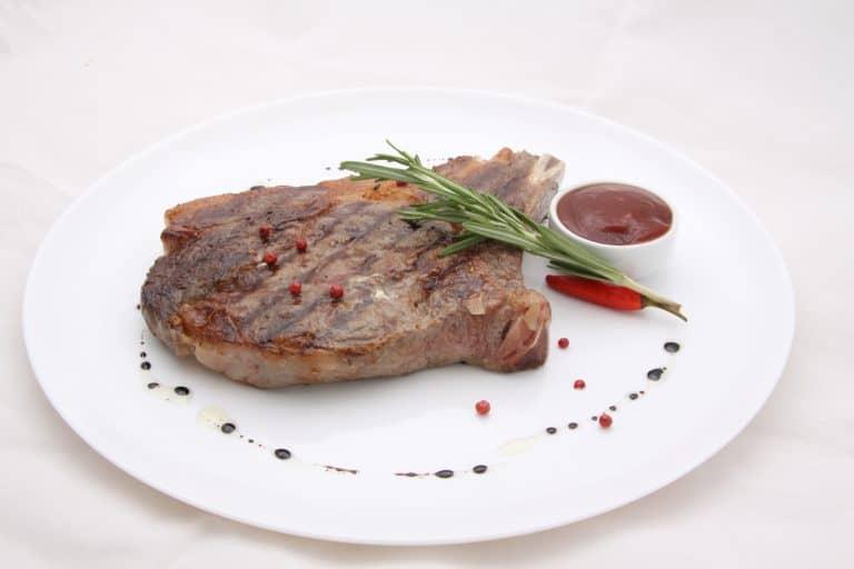 Steak resting on white plate