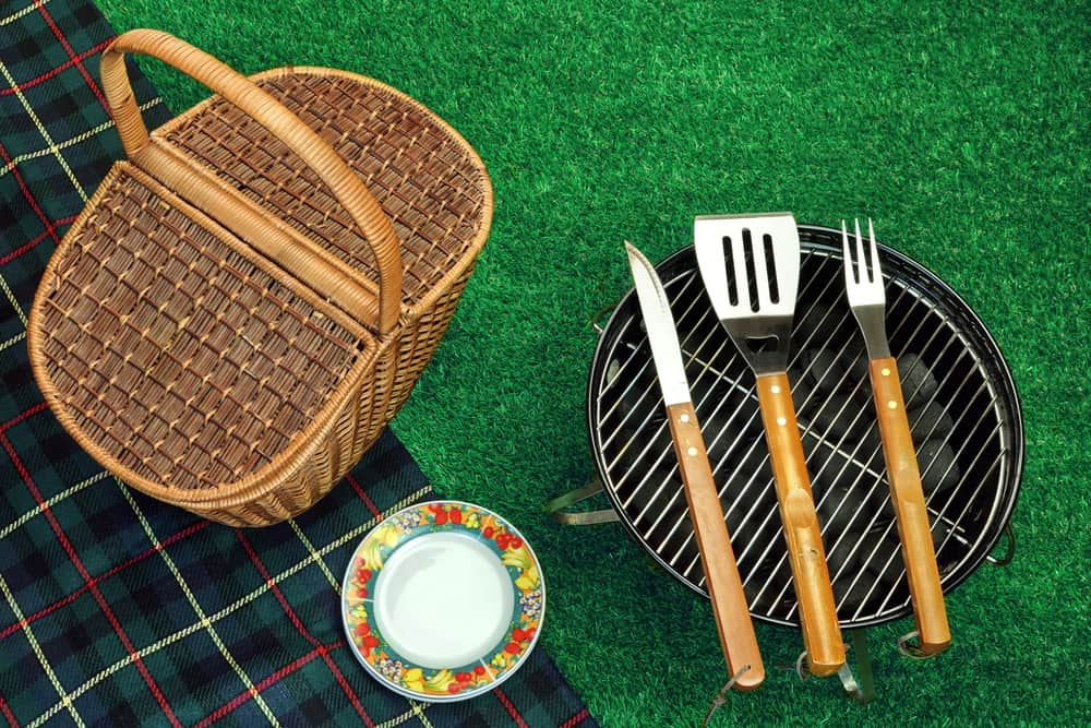 Portable BBQ, utensils, and picnic basket on grass