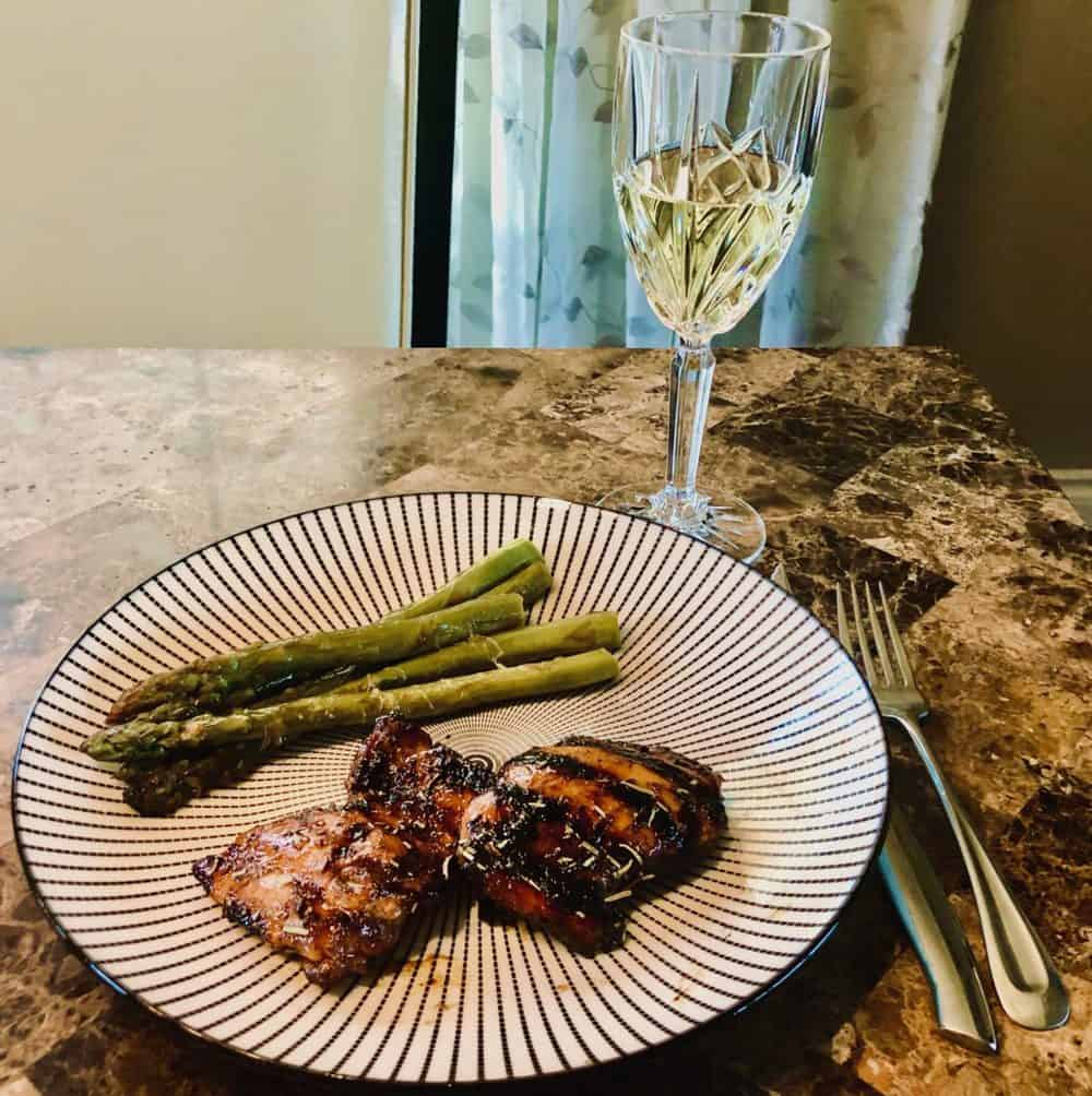 Grilled chicken, grilled asparagus plated with a glass of white wine