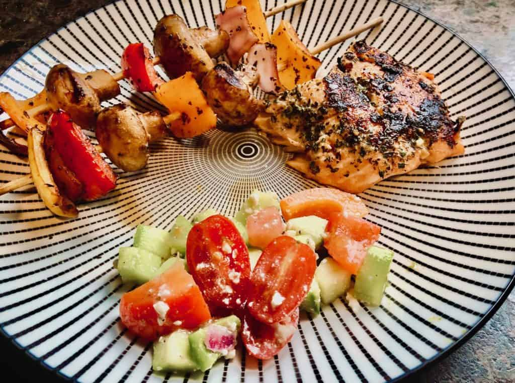 Grilled salmon, veggie skewers, greek salad
