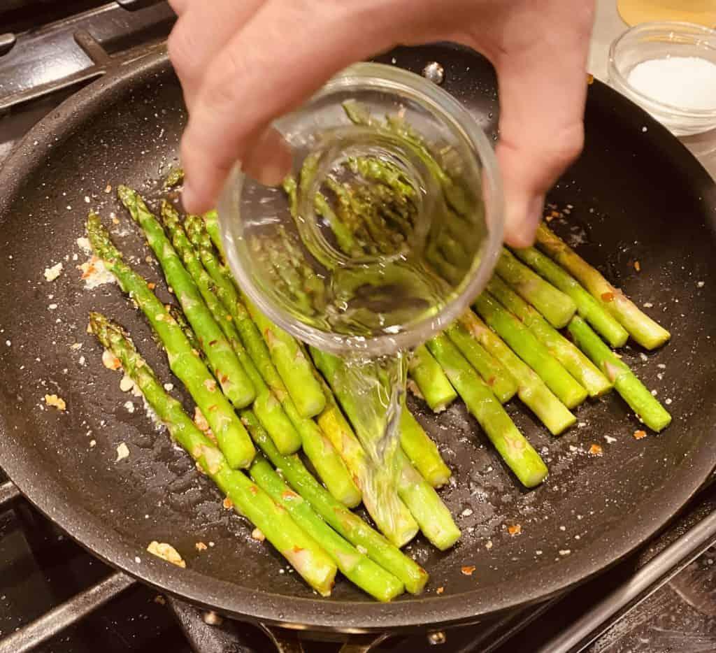 Addiing white wine vinegar to asparagus